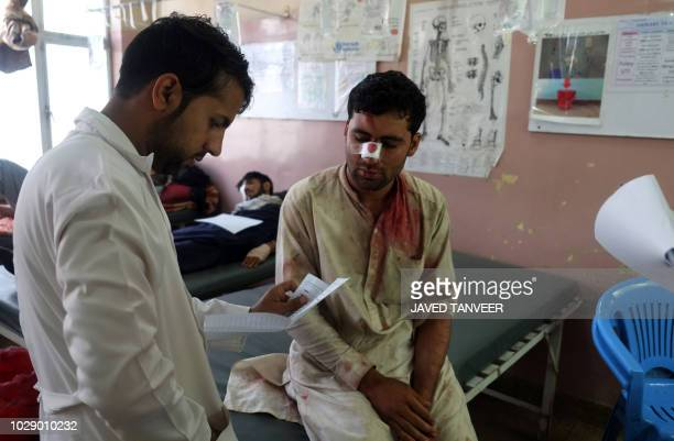 A wounded Afghan passenger is treat at a hospital after a bus and truck collided in Kandahar province on September 8 2018 At least 13 people were...