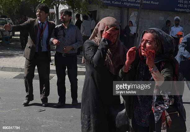 TOPSHOT Wounded Afghan women and men gesture at the site of a car bomb attack in Kabul on May 31 2017 At least 40 people were killed or wounded on...