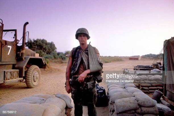 Wounded American Marine stands with his arm in a sling between a sandbag emplacement and a military truck, Beirut, Lebanon, 1982. The US Marines were...