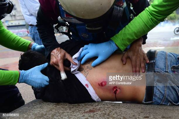 A wounded antigovernment activist is assisted by medics during clashes with the police which erupted during a protest against the elections for a...