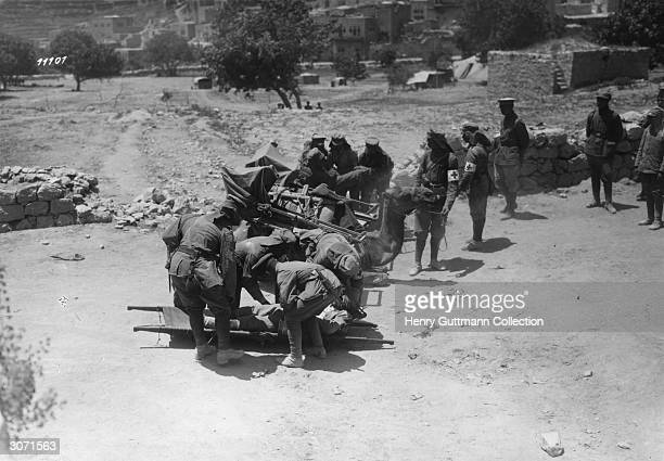Wounded being loaded onto camels by the Red Cross during the Palestine campaign in WWI