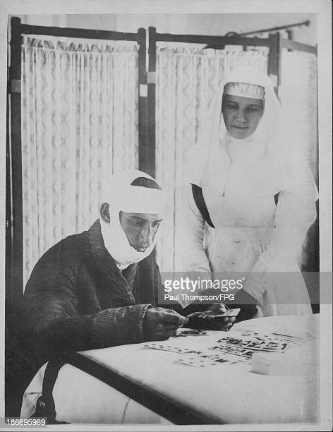 A wounded Belgian soldier with a British nurse undergoing convalescence during World War One Great Britain circa 19141918