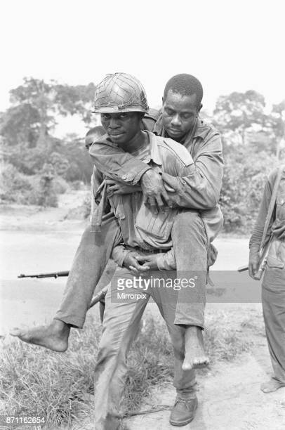 A wounded Biafran soldier is given a piggyback to a field dressing station following an attack by the Nigerian army 11th June 1968