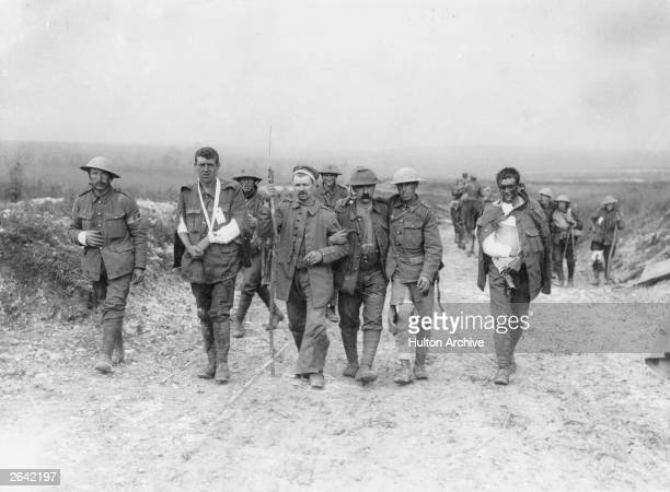 Wounded British prisoners being escorted by a German soldier on the Menin Road