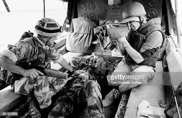 Wounded British Royal Marine Kevin Jones of 539 Assault Squadron receives treatment from Sergeant Gary Higson as BBC cameraman Steve Gray films the...