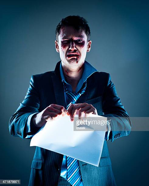 Wounded businessman tearing paper