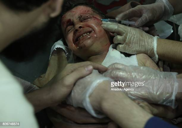 A wounded child receives medical treatment with a syringe after Assad Regime's forces attacked with missiles over the deconflict zone Ayn Tarma town...