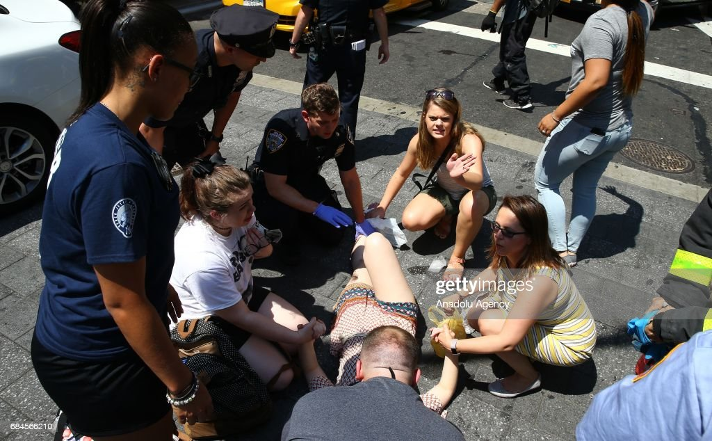 A wounded civilian receives first aid on the ground after a maroon sedan vehicle plowed into pedestrians on a busy sidewalk on the corner of West 45th St. and Broadway at Times Square, New York, NY United States on May 18, 2017. Multiple pedestrians were struck Thursday by a speeding vehicle in the heart of New York City, according to reports. At least 1 people dead and 19 others wounded.