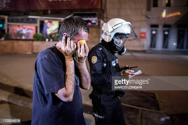 A wounded demonstrators presses a lemon against his eye while being led away by a Turkish police officer in central Ankara June 11 2013 during...