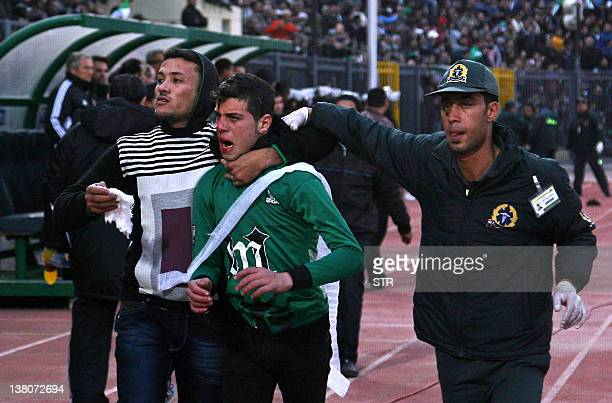 A wounded Egyptian fan of AlMasry is escorted by a medic and a friend following clashes between rival football fans after a football match between...