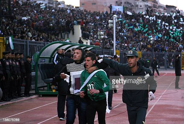 Wounded Egyptian fan of Al-Masry is escorted by a medic and a friend following clashes between rival football fans after a football match between...