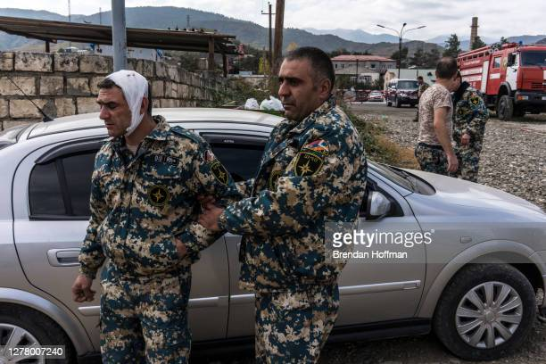 Wounded emergency services member is escorted by a colleague after a bomb fell outside a fire station on October 2, 2020 in Stepanakert,...