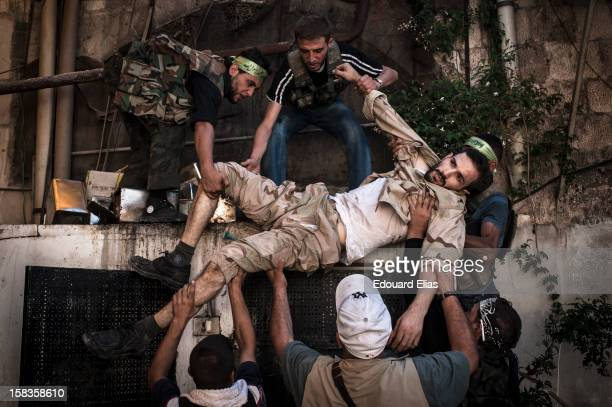 AUGUST 20 A wounded Free Syrian Army fighter is carried to safety in the old citadel of Aleppo on August 20 2012 in Aleppo Syria Government forces...