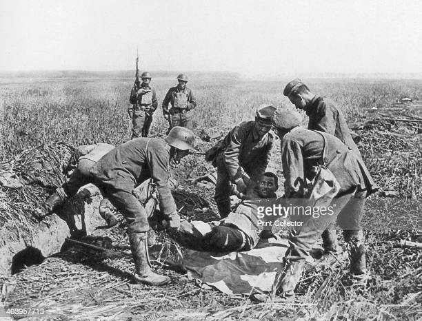 Wounded German soldier being moved by prisoners Aisne France 18 July 1918 Two American infantrymen look on