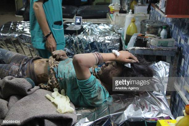 A wounded girl pulled out of the debris receives treatment at a field hospital after airstrikes hit Khan Sheikhun town of Idlib Syria on September 21...