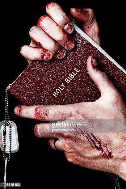 wounded hands clenching bible - soldier praying stock photos and pictures