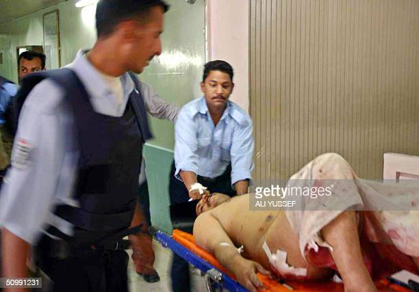 A wounded Iraqi policeman is wheeled by colleagues into a hospital in Baquba 60 kms northeast of Baghdad 24 June 2004 Nineteen people including 11...