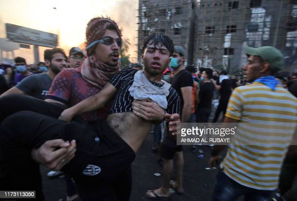A wounded Iraqi protester is carried by a comrade during a demonstration against state corruption failing public services and unemployment at Tayaran...