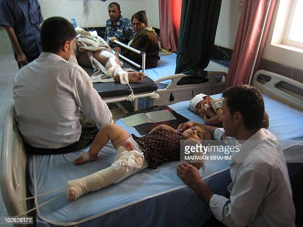 Wounded Iraqis lie on their hospital beds in the northern oil hub of Kirkuk after a suicide bomber in a car set off his payload outside a government...
