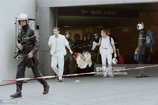 Wounded is carried away by firemen and medics at the entrance of the Orsay Museum train station after a bomb attack on a rush-hour commuter train on...
