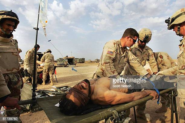 A wounded Jordanian Jihad fighter is treated by medics from the US Army 1st Infantry Division 22 Task Force on November 14 2004 in Fallujah Iraq The...