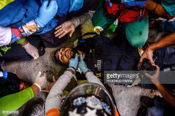 A wounded journalist is helped by volunteer medics during clashes between opposition demonstrators and riot police ensuing an antigovernment protest...