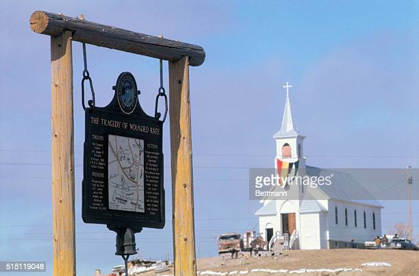 Wounded Knee South Dakota Sign in foreground commemorate Wounded Knee Massacre of 1890 American Indian Movement fortifications around Sacred Heart...