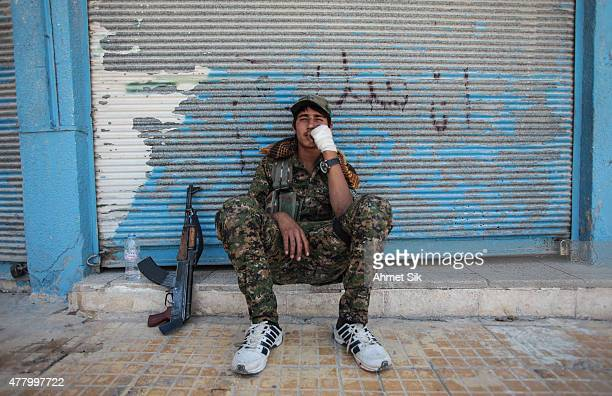 A wounded Kurdish People's Protection Units or YPG fighters rests at downtown of Tal Abyad Syria June 19 2015 Kurdish fighters with the YPG took full...