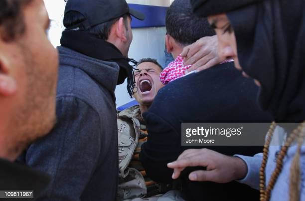 Wounded Libyan militiaman is loaded into an ambulance after being injured on the frontline with government troops on March 6, 2011 in Ben Jawat,...