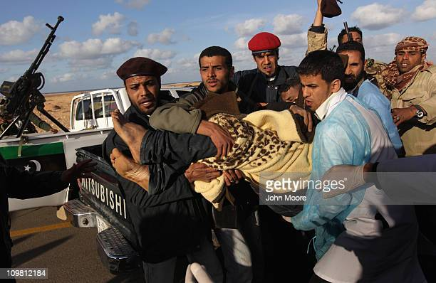 Wounded Libyan rebel militiaman is carried to an ambulance after being injured on the frontline with government troops on March 6, 2011 in Ben Jawat,...