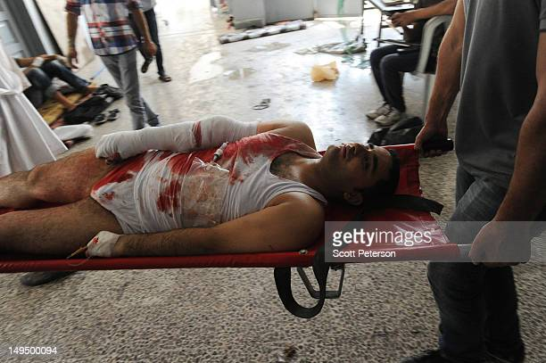 A wounded man is carried on a stretcher as casualties mount from intense shelling on the first day of a Syrian government military offensive against...