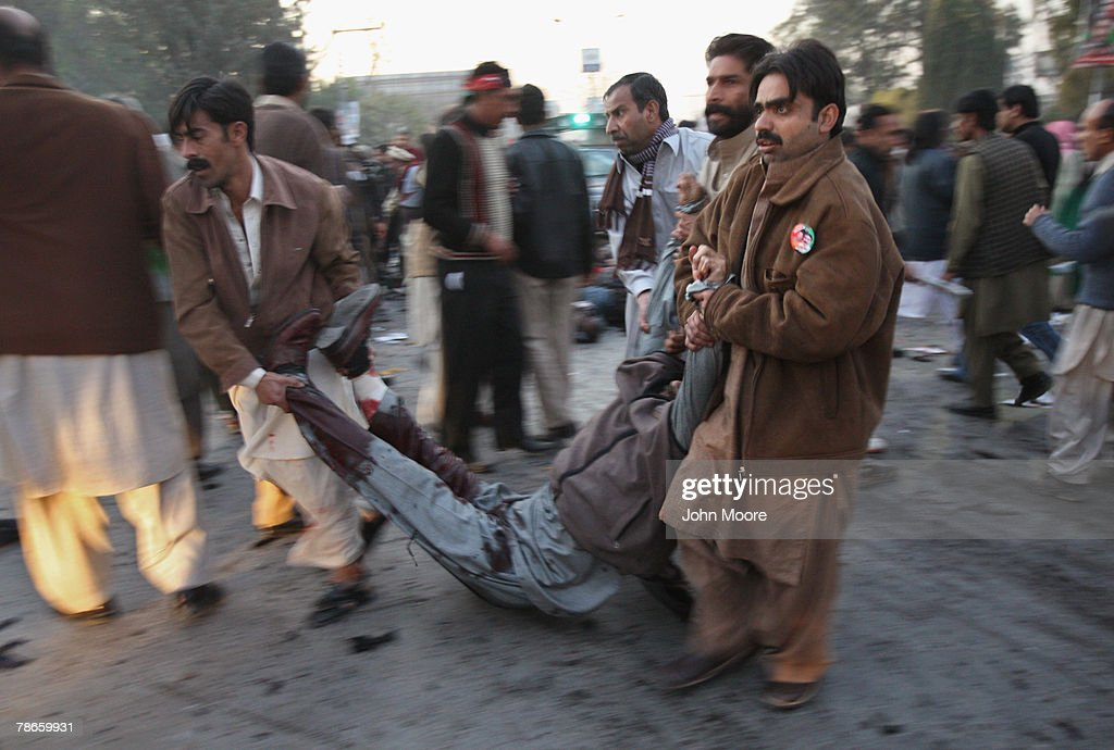 A wounded man is carried to an ambulance following a bomb attack on former Prime Minister Benazir Bhutto December 27, 2007 in Rawalpindi, Pakistan. The opposition leader has died from a bullet wound to the neck after speaking at an election rally in the northern city where an estimated 15 people were left dead by the explosion, a party official and Bhutto's husband have been quoted as saying.