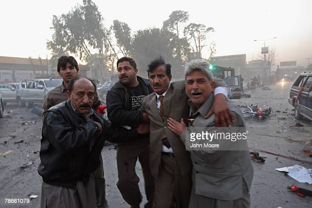 A wounded man is helped away from the site of an assassination attack on former Prime Minister Benazir Bhutto December 27 2007 The opposition leader...