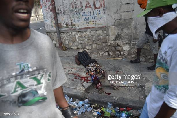 TOPSHOT A wounded man lies on a road following clashes with Haitian Police during a protest against the increase in fuel prices July 7 2018 in...