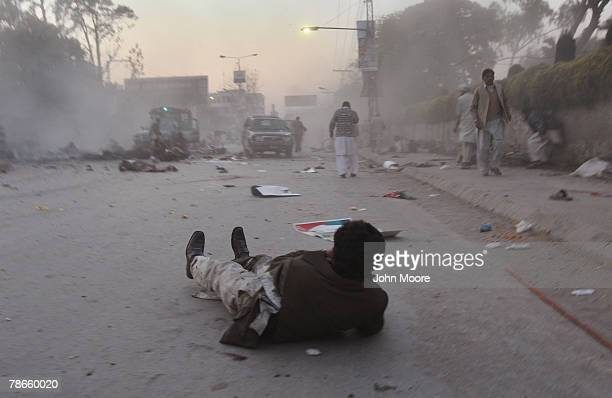 Wounded man looks towards the site of a bomb attack on former Prime Minister Benazir Bhutto on December 27, 2007 in Rawalpindi, Pakistan. The...