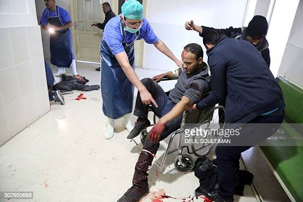 Wounded man receives the first aid at the hospital of Alkalima on December 30, 2015 in Qamishli, after three separate explosions that killed at least...