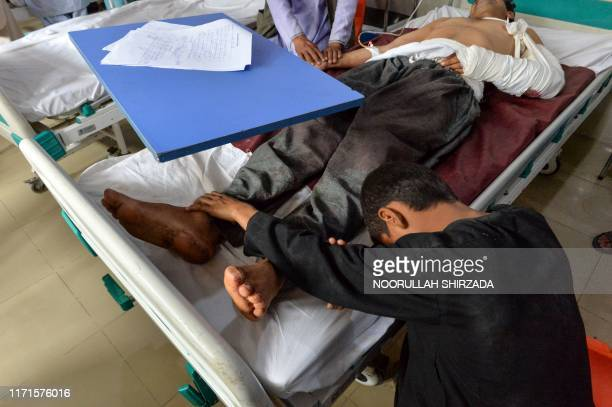 Wounded man receives treatment at a hospital after a blast as his son touches his feet in Jalalabad on September 28, 2019. - Insurgents worked to...