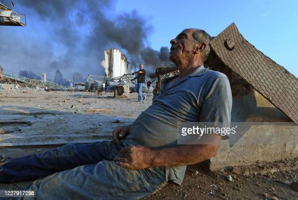 Wounded man sits on the ground waiting for aid at Beirut's port following a massive explosion that hit the heart of the Lebanese capital on August 4,...