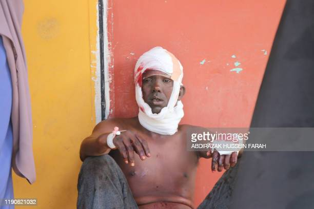 TOPSHOT A wounded man sits outside of emergency unit at Mogadisghu's Madina Hospital in Mogadishu on December 28 2019 A massive car bomb exploded in...