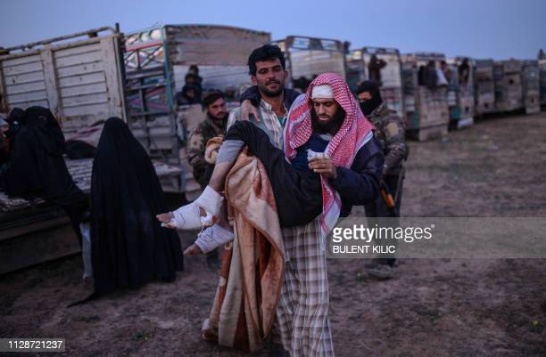 A wounded man suspected of belonging to the Islamic State group is carried before being searched by members of the Kurdishled Syrian Democratic...