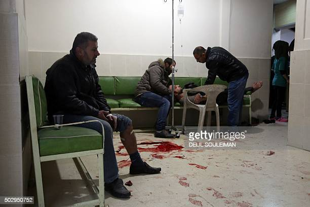 A wounded man waits to receive first aid at the hospital of Alkalima on December 30 2015 in Qamishli after three separate explosions that killed at...