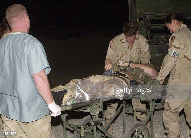 A wounded member of the US Special Forces is carried out of the military ambulance into a military hospital November 28 2002 at Bagram Airbase in...