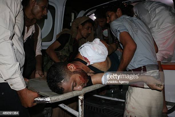 Wounded men are carried to hospitals after the clashes between the Houthi Ansarullah movement members and the people's opposition forces supporting...