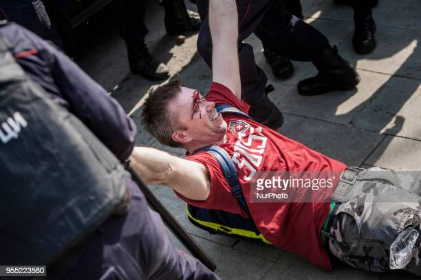 Wounded Navalny supporter is arrested by riot police in a demonstration against Putin in Pushkin square Moscow Russia on 5 May 2018