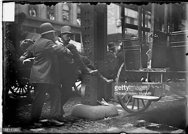 Wounded nonunion driver being carried to an ambulance by two policemen during the 1902 Teamsters Strike Chicago Illinois June 4 1902