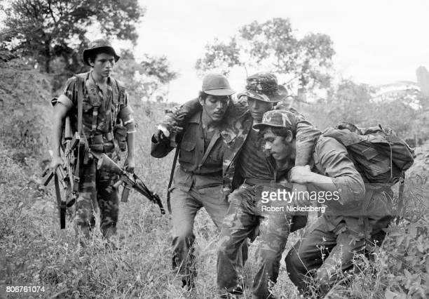 Wounded officer, 2nd right, from the Atlacatl Battalion is evacuated by soldiers during a military operation pursuing guerrillas from the Farabundo...