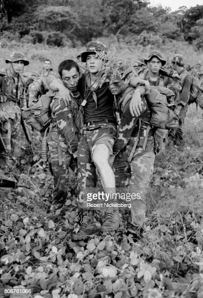 A wounded officer from the Atlacatl Battalion is evacuated by fellow soldiers during a military operation pursuing guerrillas from the Farabundo...