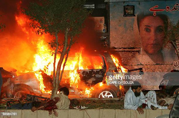 Wounded Pakistani men wait for help on the site of a blast site near the convoy of former prime minister Benazir Bhutto in Karachi late 18 October...
