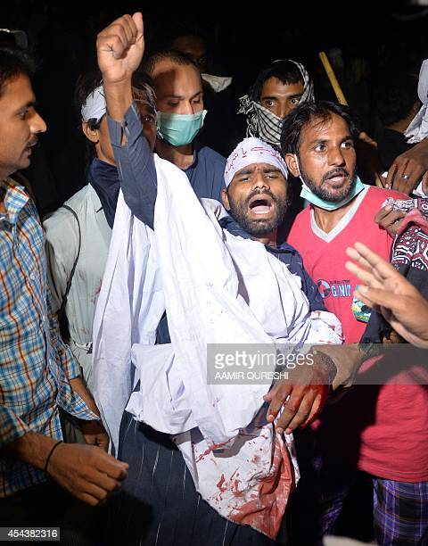 A wounded Pakistani opposition supporter shouts slogans as he is helped by fellow protesters following clashes with security forces near the prime...