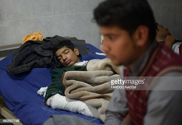 Wounded Pakistani student Mehran rests on a hospital bed after Taliban gunmen attacked a school in Peshawar on December 17 2014 Militants rampaged...